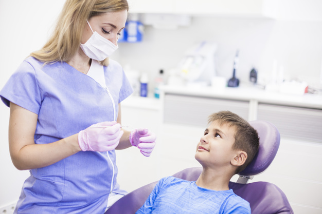 female-dentist-with-surgical-mask-holding-scaler-near-patient-clinic_23-2147905998